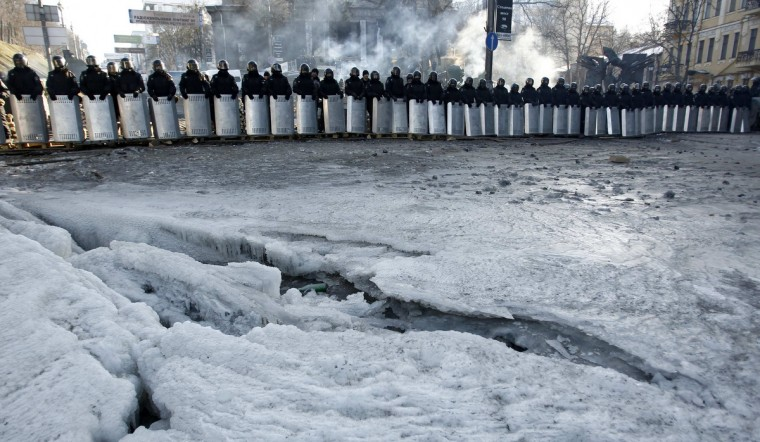 Riot police stand in a cordon facing a barricade of anti-government protesters in Kiev.The confrontation between opposition-led protesters and the government of President Viktor Yanukovich, and a refusal to agree a compromise, is weighing on the Ukrainian economy, acting prime minister Serhiy Arbuzov said on Wednesday. (David Mdzinarishvili/Reuters)