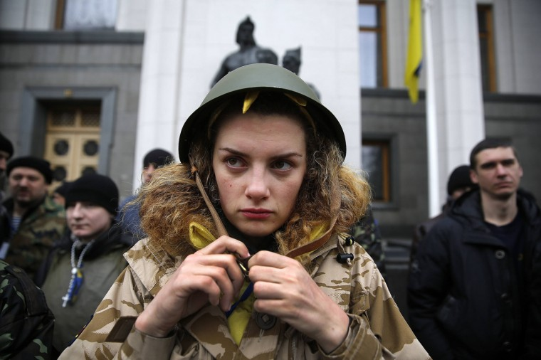 An anti-Yanukovich protester buckles her helmet as she stands guard outside the parliament building along with her comrades in Kiev. Activists gathered outside parliament in Kiev as deputies vote for a new national unity government to govern the country until elections in May. Ukraine's protest leaders on Wednesday named the ministers they want to form a new government following the overthrow of President Viktor Yanukovich. (Yannis Behrakis/Reuters)