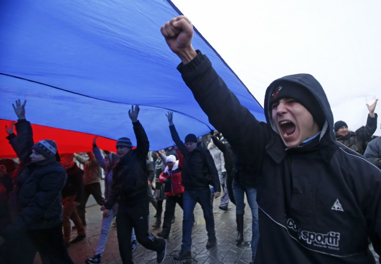 People march under a giant Russian flag during a pro-Russian rally in Simferopol, Crimea. Armed men seized regional government headquarters and parliament in Ukraine's Crimea on Thursday and raised the Russian flag, alarming Kiev's new rulers, who urged Moscow not to abuse its navy base rights on the peninsula by moving troops around. (David Mdzinarishvili/Reuters)