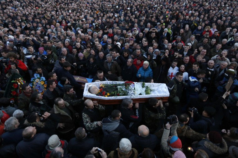 People attend the funeral of an anti-government protester who was killed during Thursday's clashes with riot police, in Kiev February 21, 2014. Ukraine's opposition leaders signed an EU-mediated peace deal with President Viktor Yanukovich on Friday, aiming to resolve a political crisis in which dozens have been killed and opening the way for an early presidential election this year. (REUTERS/Baz Ratner)