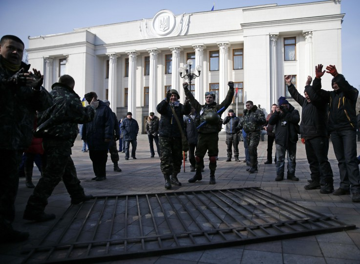 Members of self-defence units react after demolishing a fence enclosing the parliament building in Kiev February 26, 2014. Ukraine's acting president Oleksander Turchinov has assumed the duties of head of the armed forces, the presidential website said on Wednesday. (REUTERS/David Mdzinarishvili)