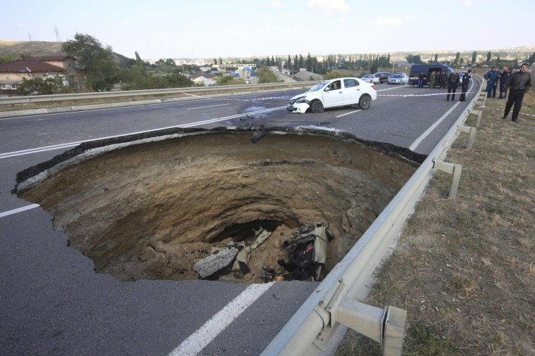 A car rests in a sinkhole in the road outside the Crimean capital Simferopol, September 28, 2014.A sinkhole about eight meters wide and deep opened up on Saturday night on the road between Nikolayev and Yevpatoria highway; killing six people tavelling in a car which fell into the pit, according to local media. (Pavel Rebrov/Reuters)