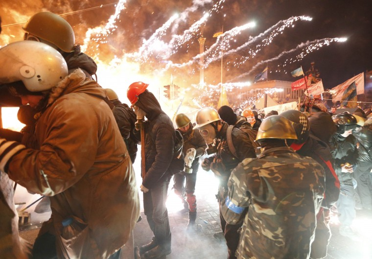 Fireworks explode near anti-government protester during clashes with riot police at the Independence Square in Kiev February 18, 2014. Ukrainian riot police advanced on Tuesday onto a central Kiev square occupied by protesters, after at least 14 people died in the worst day of violence since demonstrations erupted against President Viktor Yanukovich 12 weeks ago. REUTERS/Vasily Fedosenko