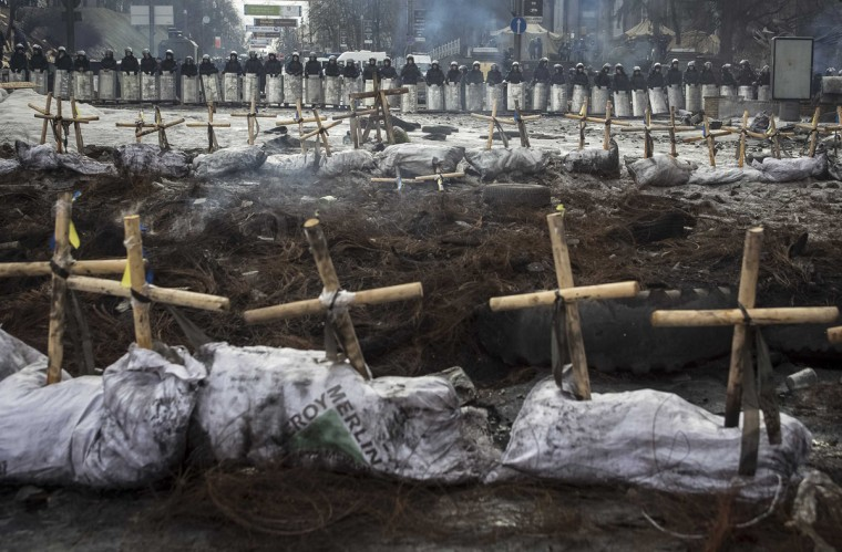 """Riot police stand behind crosses installed by anti-government protesters in memory of the people who have died and went missing during clashes in Ukraine, near the barricades in Kiev February 11, 2014. Ukrainian protesters, now in their third month of action, kept up pressure on President Viktor Yanukovich on Sunday with a mass rally where opposition leaders called for an end to his """"dictatorial"""" powers. (Konstantin Grishin/Reuters)"""