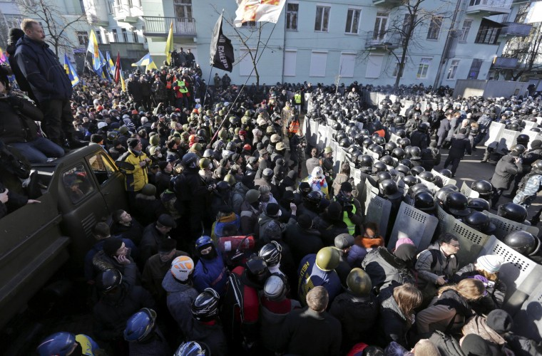 Demonstartors stand against police during a protest in Kiev February 18, 2014. Ukrainian riot police advanced on the heart of 12-week-old protests against President Viktor Yanukovich on Tuesday and security forces set a deadline to end disturbances after at least five protesters were reported killed in a day of clashes. (REUTERS/Konstantin Chernichkin)