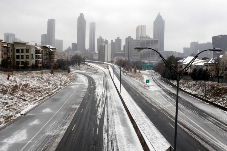 The road is empty leading out of downtown Atlanta as drivers heeded advice to not drive during an ice storm in Atlanta, Georgia, February 12, 2014. A deadly winter storm brought heavy snow, freezing rain and a possibly historic accumulation of ice to the southeastern United States on Wednesday, causing hundreds of thousands of power outages and treacherous driving conditions, meterologists said. (REUTERS/Tami Chappell)