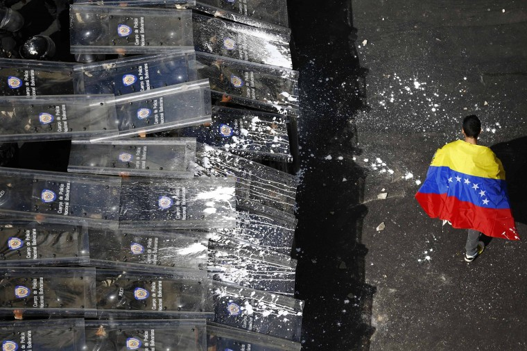 A demonstrator with a Venezuelan flag draped around himself protests against the government of Venezuela's President Nicolas Maduro, in front of a riot police line in Caracas February 12, 2014. (REUTERS/Jorge Silva)