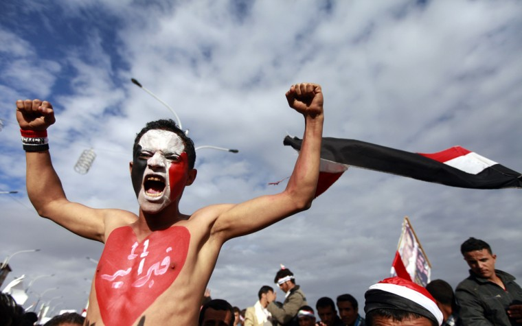 """A pro-democracy demonstrator shouts slogans during a celebration to mark the anniversary of an uprising against the regime of former president Ali Abdullah Saleh in Sanaa February 11, 2014. The characters on his chest read """"February 11."""" (Mohamed al-Sayagh/Reuters)"""