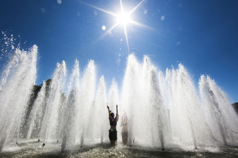 Gymnasts play in a fountain to cool down on the second day of the World Gymnaestrada in Lausanne, Switzerland on July 11, 2011. (REUTERS/Valentin Flauraud)