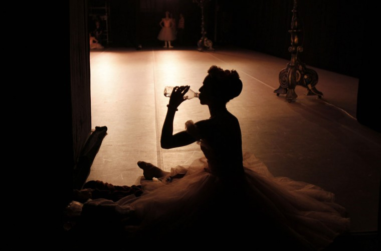 A Cuban National Ballet ballerina drinks water during the Cuban National Ballet Gala concert at the Bolshoi Theatre in Moscow on Aug. 2, 2011. (REUTERS/Denis Sinyakov)