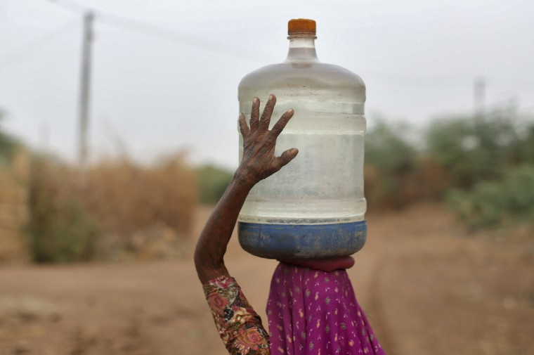 A village woman carries a container filled with drinking water supplied by the government-run water tanker at Charanka village in the western Indian state of Gujarat on Aug. 5, 2012. (REUTERS/Ahmad Masood)