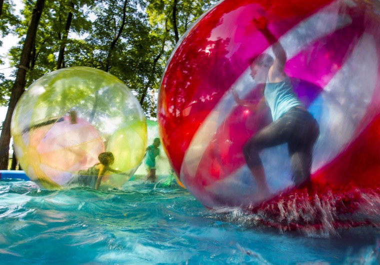 Children play in aqua-zorbing balls in a temporary inflatable pool in the garden of the Chancellery during open house day in Berlin on Aug. 19, 2012. (REUTERS/Thomas Peter)