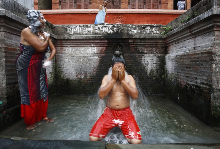 Locals take a bath at a stone spout in Lalitpur, Nepal on Sept. 25, 2012. (REUTERS/Navesh Chitrakar)