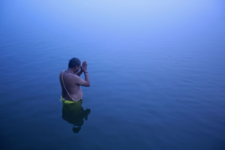 A Hindu devotee stands in the waters of river Ganges to offer prayers to the Sun god at dawn in Varanasi, in the northern Indian state of Uttar Pradesh on Jan. 12, 2013. (REUTERS/Danish Siddiqui)