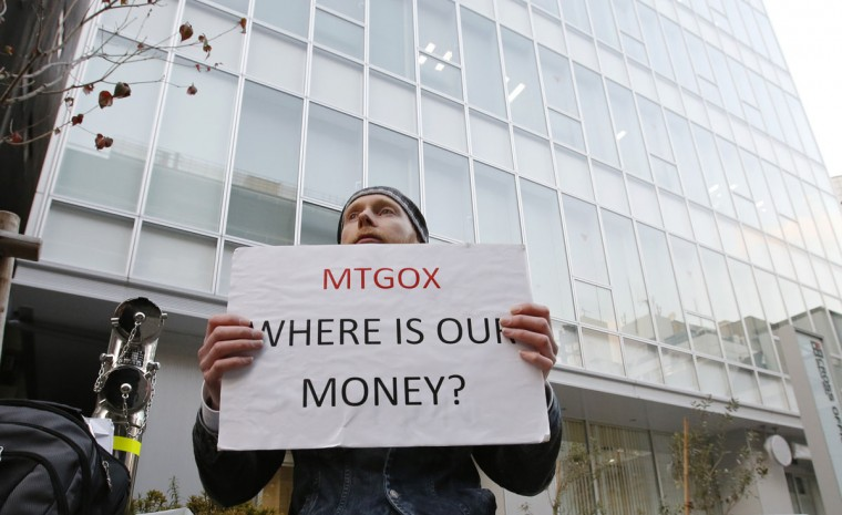 Kolin Burges, a self-styled cryptocurrency trader and former software engineer who came from London, holds a placard to protest against Mt. Gox, in front of the building where the digital marketplace operator is housed in Tokyo. The website of Mt. Gox appears to be taken down, shortly after six major Bitcoin exchanges released a joint statement distancing themselves from the troubled Tokyo-based bitcoin exchange. (REUTERS/Toru Hanai)