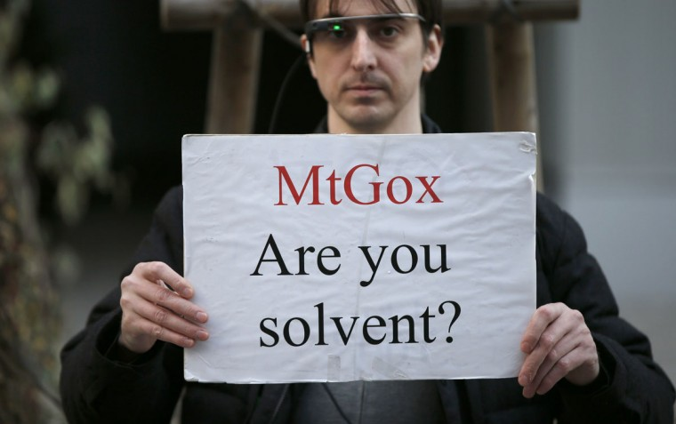 Protester Aaron holds a placard during a demonstration against Mt. Gox, in front of the building where the digital marketplace operator is housed, in Tokyo. The website appears to be taken down, shortly after six major Bitcoin exchanges released a joint statement distancing themselves from the troubled Tokyo-based bitcoin exchange. (REUTERS/Toru Hanai)