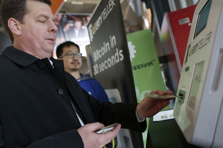 Dave Mitchell (left) purchases bitcoin at the Liberty Teller kiosk as Liberty Teller co-founder Chris Yim looks on at South Station in Boston on February 25, 2014. (REUTERS/Dominick Reuter)