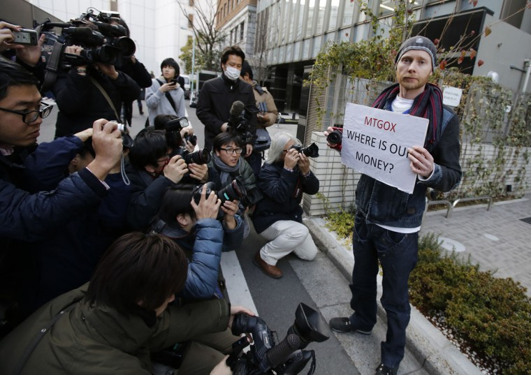 Kolin Burges (right), a self-styled cryptocurrency trader and former software engineer from London, holds a placard to protest against Mt. Gox, as photographers take photos of him in front of the building where the digital marketplace operator was formerly housed in Tokyo. (REUTERS/Toru Hanai)