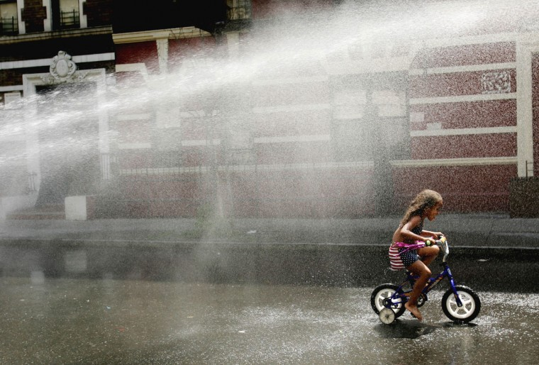 A young girl rides a tricycle under a cascade of water from an open fire hydrant along 151st Street in upper Manhattan on July 26, 2005. (REUTERS/Mike Segar)