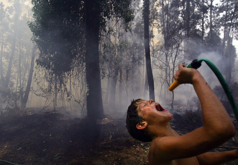 A child drinks water during a forest fire in Salceda de Caselas, in northern Spain on Aug. 23, 2005. (REUTERS/Miguel Vidal)