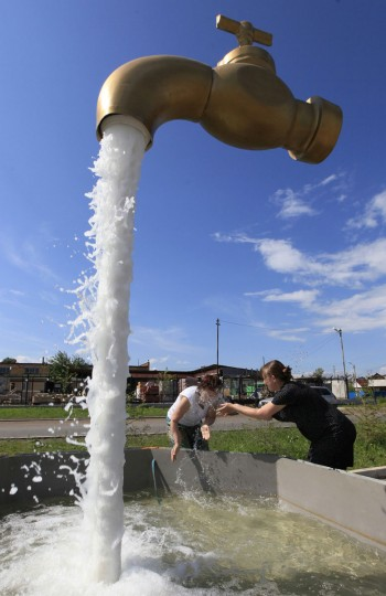 A fountain depicting a water tap is on display in the suburbs of Russia's Siberian city of Krasnoyarsk on July 9, 2013. (REUTERS/Ilya Naymushin)