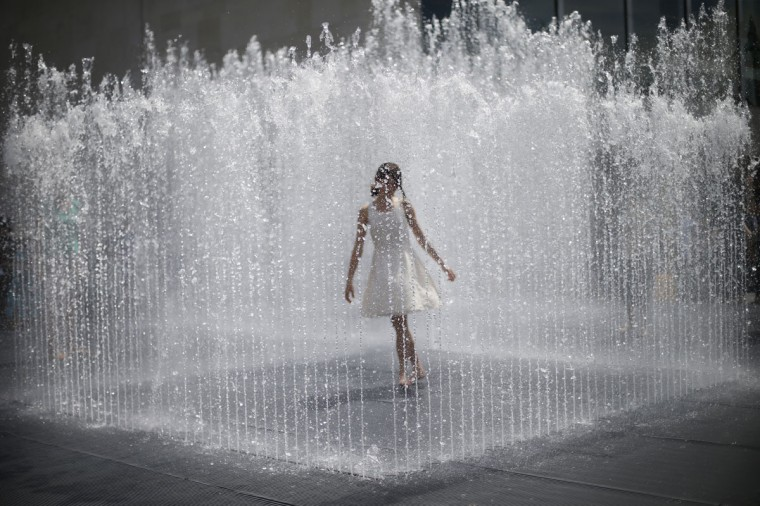 A girl stands surrounded by the jets of a fountain on the South Bank on a hot summer day in central London on July 15, 2013. (REUTERS/Andrew Winning)