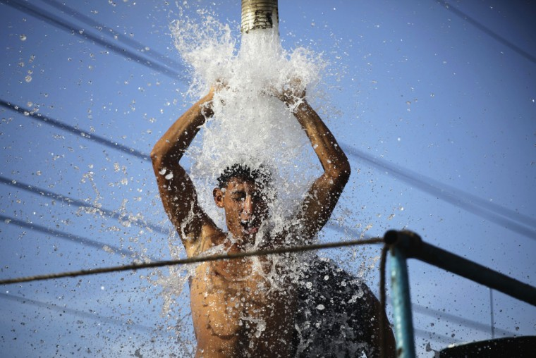 A laborer cools down under water from a supply pump in a truck on the outskirts of Havana on Sept. 5, 2013. (REUTERS/Desmond Boylan)