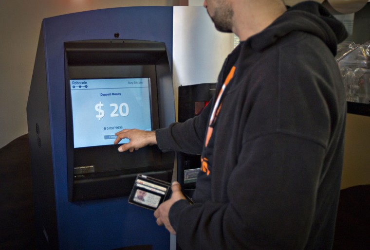 A customer uses the world's first ever permanent bitcoin ATM, unveiled at a coffee shop in Vancouver, British Columbia on October 29, 2013. (REUTERS/Andy Clark)
