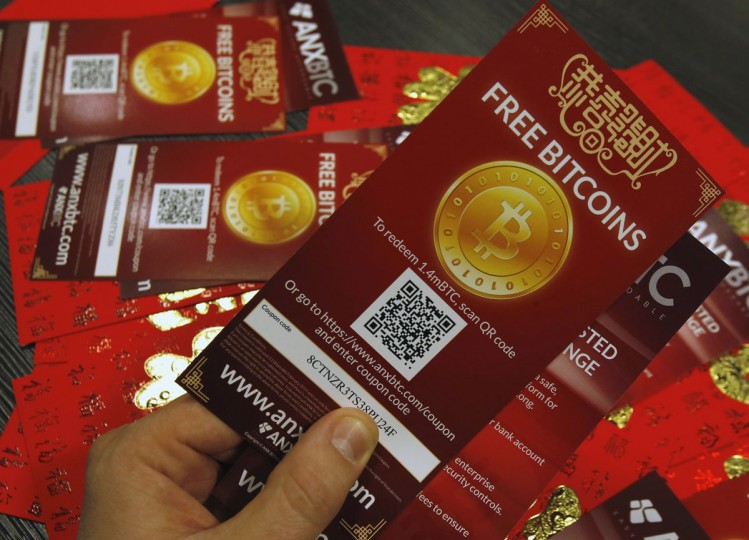 "An employee of a bitcoin exchange company displays bitcoin vouchers, which are worth around $1.15, in Hong Kong on February 11, 2014. About 50,000 such vouchers were distributed as ""lai see"" or red packets during the Lunar New Year in the territory to promote the use of bitcoin. (REUTERS/Bobby Yip)"