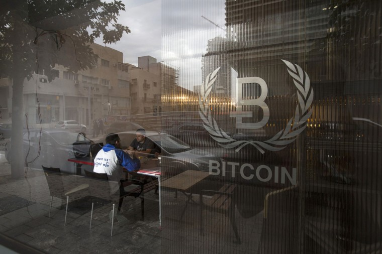 People sit inside the Bitcoin Embassy in Tel Aviv on February 2, 2014. The sparely furnished property opened a few months ago to support a community of Bitcoin fanatics, perhaps the most active in the world, who are out to build just that - a next-generation trading system based on the digital currency. (REUTERS/Baz Ratner)