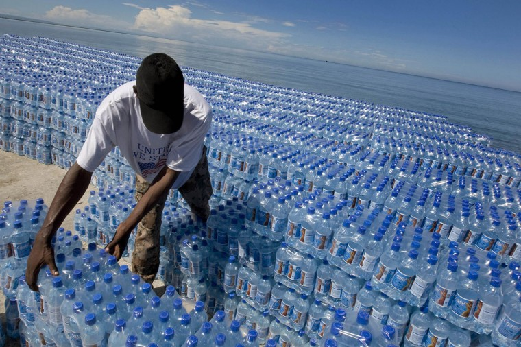 A Haitian man unloads water donated by the World Food Program at a private port after Tropical Storm Hanna passed through the region, dumping heavy rains that flooded the entire region in Gonaives, Haiti on Sept. 5, 2008. (REUTERS/Logan Abassi)