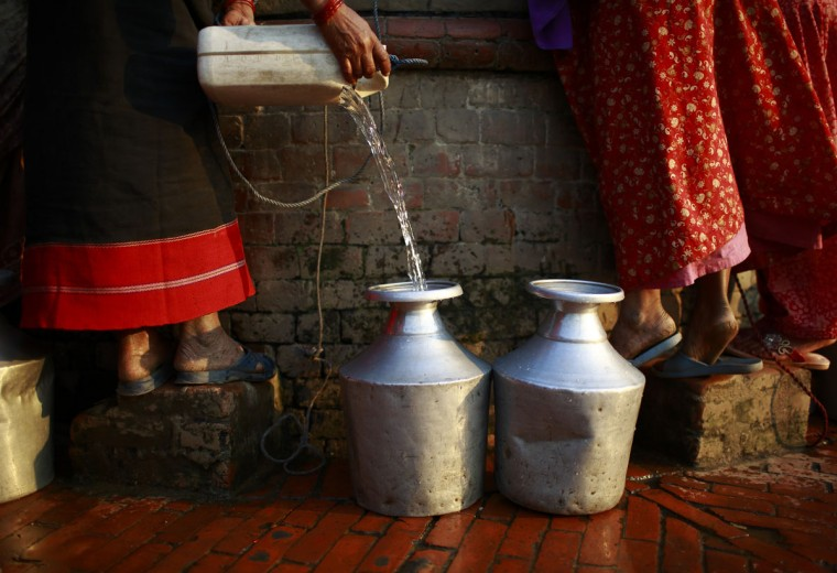 A woman fills her pot with water after pulling it out from an almost dried well in Bhaktapur, Nepal on April 4, 2013. (REUTERS/Navesh Chitrakar)