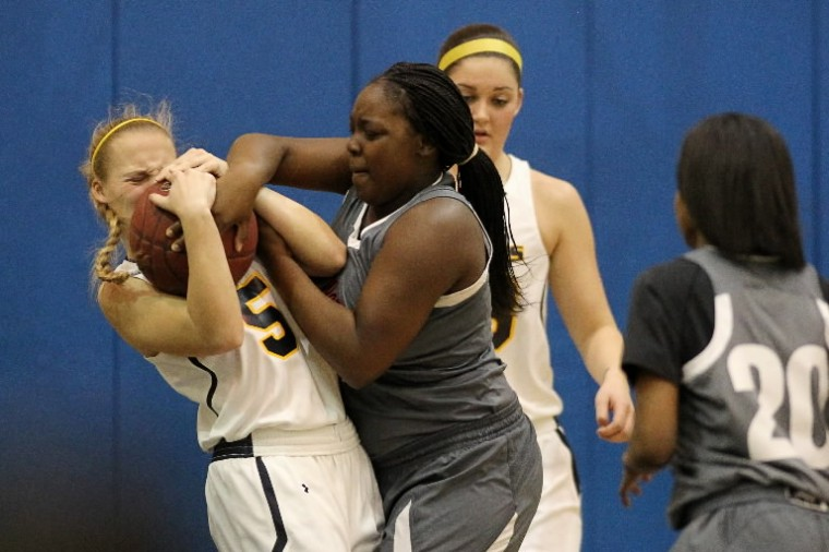 Catonsville's Lauren McDonald, left, and Woodlawn's Darshera Queen, right, battle for the ball during the girls basketball game at Catonsville High School in Catonsville Wednesday, Feb. 19. (Jen Rynda/BSMG)