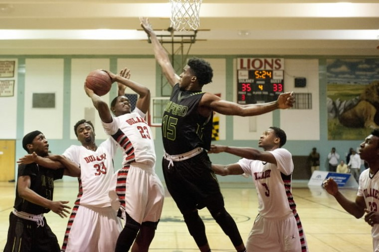Milford Mill's Elijah Cooper, center, leaps to block a shot by Dulaney's Gary Bernardez, center left, on Wednesday, Feb. 19. (Noah Scialom/BSMG)