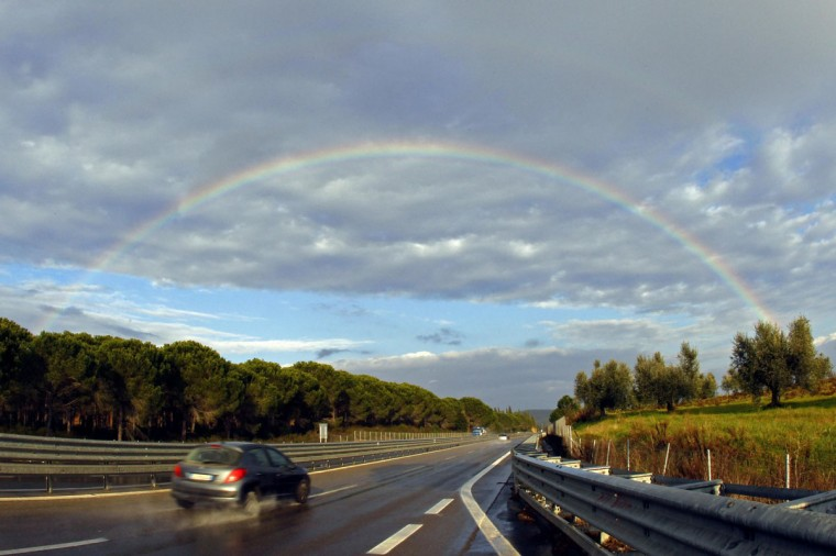 A rainbow is seen after heavy rain over the Aurelia high road in Gavorrano near Grosseto in Tuscany, Feb. 14, 2011. (Giampiero Sposito/Reuters)