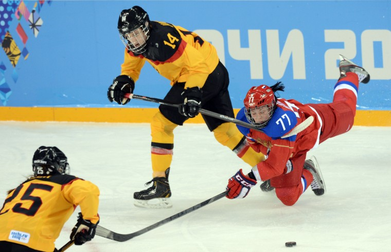 Russia defenseman Inna Dyubanok (77) falls to the ice while chasing the puck between Germany forward Jacqueline Janzen (14) and forward Franziska Busch (25) in a women's ice hockey preliminary round game during the Sochi 2014 Olympic Winter Games at Shayba Arena. (Jayne Kamin-Oncea-USA TODAY Sports)