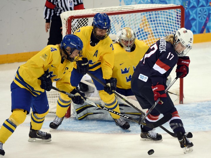 USA forward Jocelyne Lamoureux (17) reaches back for the puck while defended by Sweden forward Jenni Asserholt (4) and defenseman Johanna Olofsson (7) in a women's ice hockey semifinal during the Sochi 2014 Olympic Winter Games at Shayba Arena. (Kyle Terada/USA Today Sports)