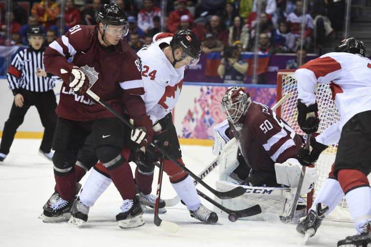 Latvia defenseman Georgijs Pujacs (81) and Canada forward Corey Perry (24) go after the puck in the men's ice hockey quarterfinals during the Sochi 2014 Olympic Winter Games at Bolshoy Ice Dome. (Richard Mackson-USA TODAY Sports)