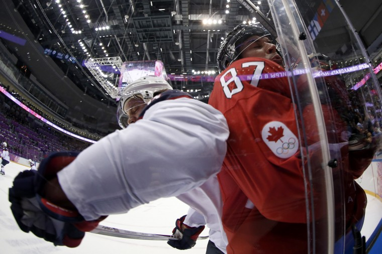 USA defenseman John Carlson (4) and Canada forward Sidney Crosby (87) collide into the boards in the men's ice hockey semifinals during the Sochi 2014 Olympic Winter Games at Bolshoy Ice Dome. (Winslow Townson-USA TODAY Sports)