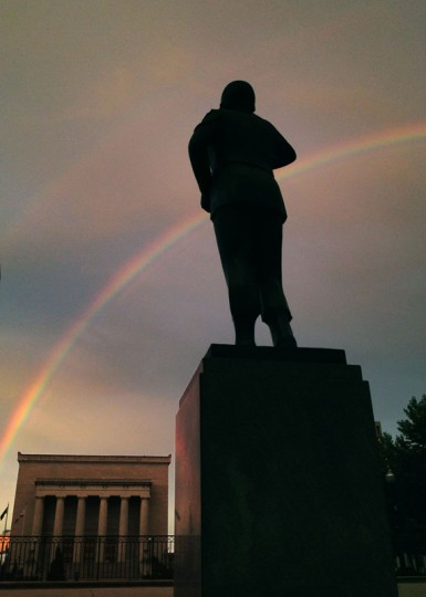 A portion of a rainbow rises above the Black Soldiers statue that looks out to War Memorial Plaza June 28, 2013. (Karl Merton Ferron/Baltimore Sun Staff)