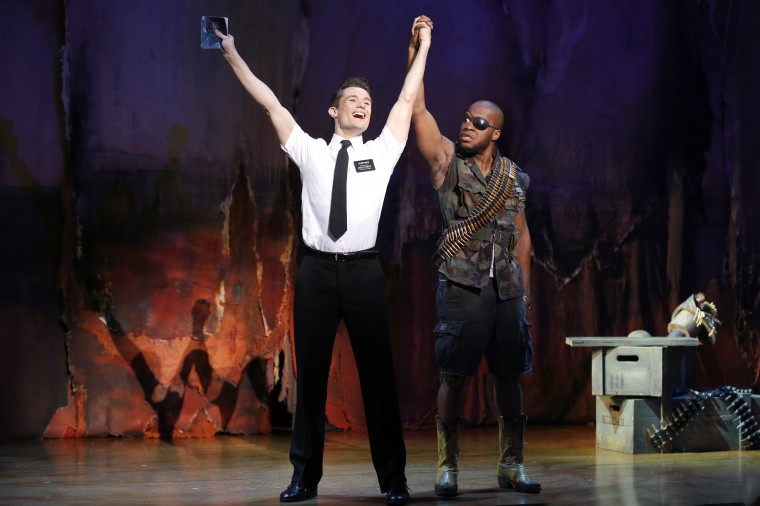 "'Mormon' wraps up: Mark Evans as missionary Elder Price; and Derrick Williams as a Ugandan warlord in ""The Book of Mormon."" The national touring production plays the Hippodrome until March 9, 2014. (Photo by Joan Marcus)"