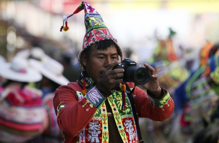 A Bolivian indigenous man takes pictures during the Anata Andina (Andean carnival) in Oruro February 27, 2014. Hundreds of ethnic groups from Oruro province participated in the carnival. (Gaston Brito/Reuters photo)