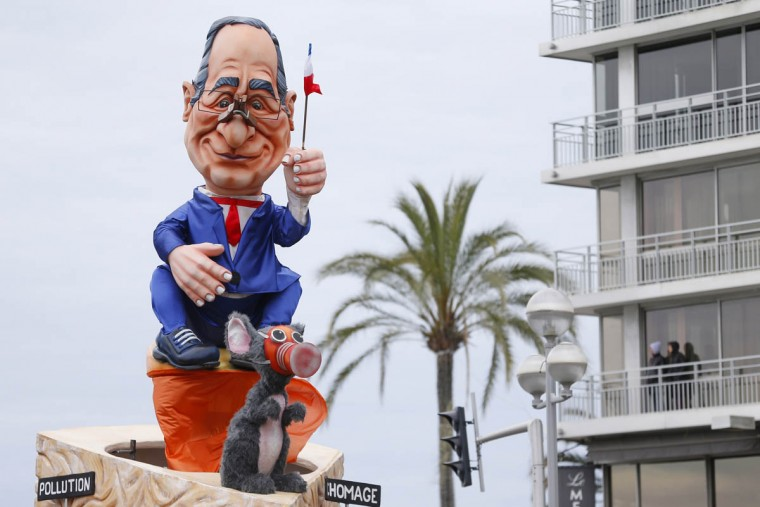"""A float named """"Cheeses of Hollande"""" and featuring French President Francois Hollande waving a French flag with a clothespin on his nose parades during the Nice Carnival on February 25, 2014 in Nice, southeastern France. The theme of this year's carnival, running from February 14 until March 4, 2014, is the """"King of Gastronomy"""". Signs on float read """"pollution"""" and """"unemployment"""". (Valery Hache/Getty Images)"""