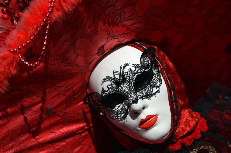 """A costumed reveller poses near St Mark's square during the carnival on February 23, 2014 in Venice. The 2014 edition of the Venice carnival is untitled """" Wonder and fantasy nature"""" and runs from February 15 to March 4, 2014. (Gabriel Bouys/Getty Images)"""