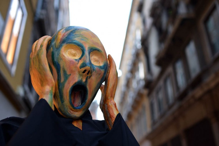 """A costumed reveller wearing a mask depicting Munch's famous painting """"The Scream"""" poses near St Mark's square during the carnival on February 21, 2014 in Venice. The 2014 edition of the Venice carnival is untitled """" Wonder and fantasy nature"""" and runs from February 15 to March 4, 2014. (Gabriel Bouys/Getty Images)"""