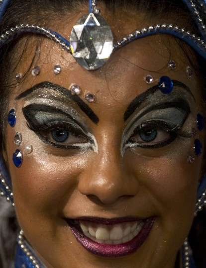 """A dancer smiles as she performs along a street of Montevideo's Sur neighbourhood, on the first night of the """"Llamadas"""" (Calls) carnival parade, on February 13, 2014. The """"Llamadas"""" is Uruguay's biggest carnival parade, in which """"comparsas"""" -- group of dancers and drummers of the traditional """"candombe"""" music -- compete in two nights of parades.(Pablo Porciuncula/Getty Images)"""