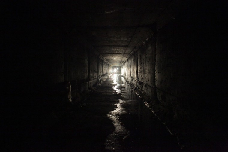 "Journalists use flashlights while walking through the city's drainage system towards a tunnel that comes out of one of the houses of Joaquin ""Chapo"" Guzman in Culiacan February 25, 2014. Guzman, who rose from humble origins to become one of the most powerful drug barons in history, was captured on Friday in Sinaloa. Picture taken February 25, 2014. (REUTERS/Daniel Becerril)"
