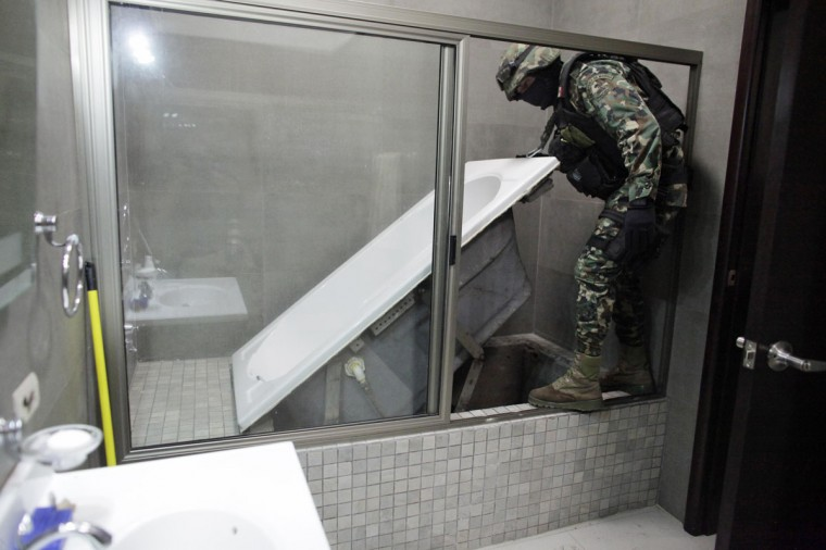 "A Mexican marine lifts a bathtub that leads to a tunnel and exits in the city's drainage system at one of the houses of Joaquin ""Chapo"" Guzman in Culiacan February 27, 2014. Guzman, who rose from humble origins to become one of the most powerful drug barons in history, was captured on Friday in Sinaloa. (REUTERS/Daniel Becerril)"