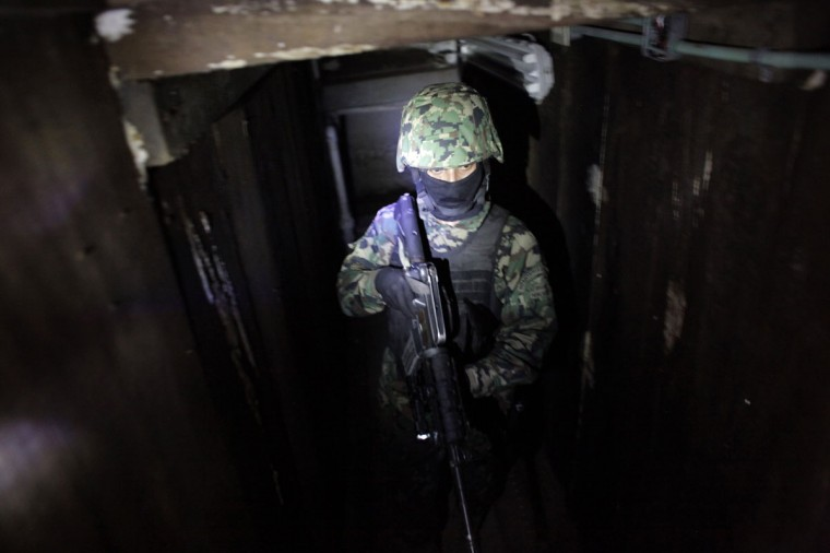 "A Mexican Marine stands in the city's drainage system after walking through a connecting tunnel underneath the houses of Mexican kingpin Joaquin ""Chapo"" Guzman during a presentation for the media n Culiacan February 27, 2014. Guzman, who rose from humble origins to become one of the most powerful drug barons in history, was captured on Friday in Sinaloa. (REUTERS/Daniel Becerril)"