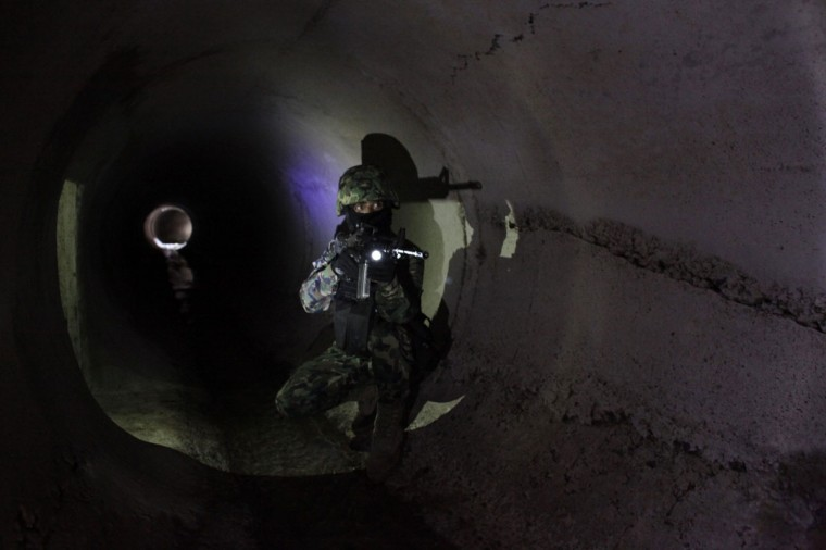 "A Mexican Marine points his weapon in the city's drainage system after walking through a connecting tunnel underneath the houses of Mexican kingpin Joaquin ""Chapo"" Guzman during a presentation for the media in Culiacan February 27, 2014. (REUTERS/Daniel Becerril)"